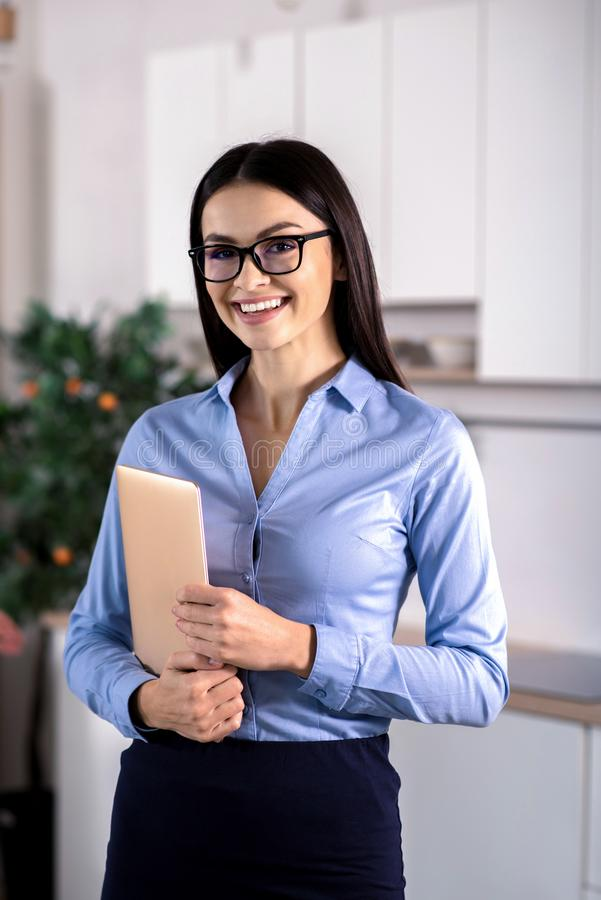 Joyful young businesswoman holding her laptop royalty free stock image