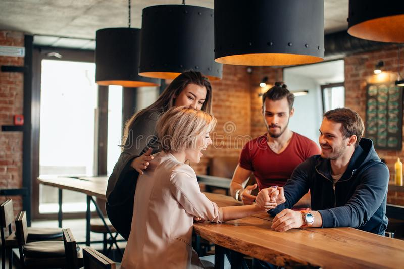 Cheerful gyu and girl having fun arm wrestling each other in pub. Joyful young couple in burger pub loughing and testing their strengths sitting at table doing stock image