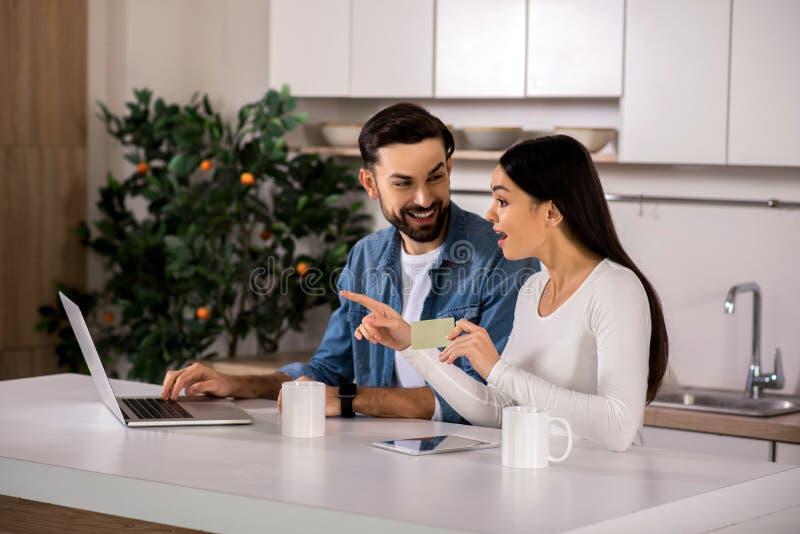 Joyful young couple using online banking royalty free stock photo