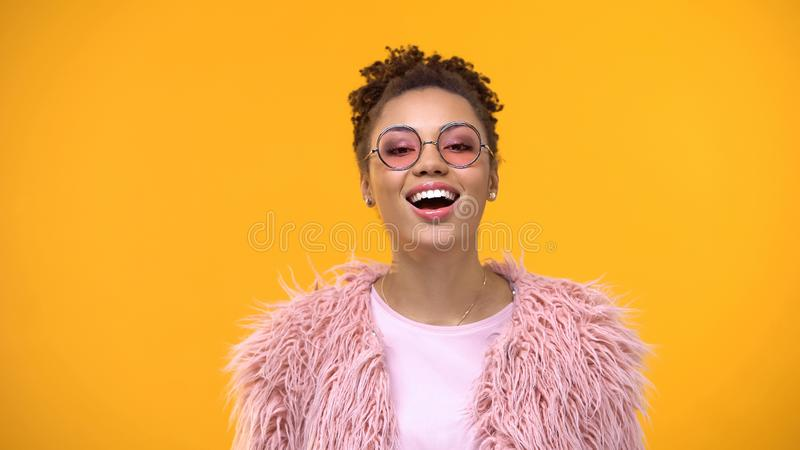 Joyful young female in fashionable eyeglasses and fur on yellow background royalty free stock images
