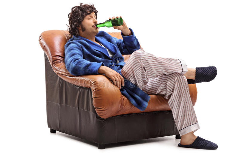 Joyful young guy drinking a cold beer. Joyful young guy sitting in an armchair and drinking a cold beer isolated on white background stock image