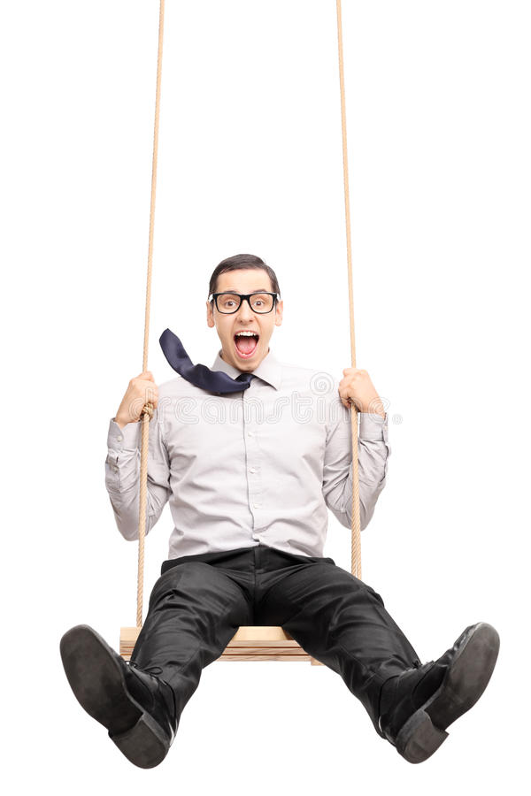 Joyful young guy swinging fast on a swing. Vertical shot of a joyful young guy swinging fast on a wooden swing isolated on white background royalty free stock photo