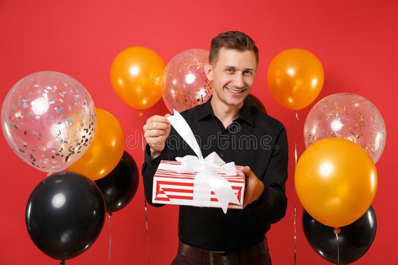 Joyful young man in black classic shirt holding, opening red box with gift, present on bright red background air royalty free stock photography