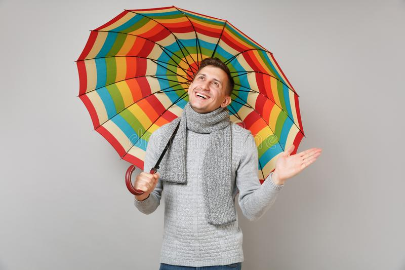 Joyful young man in gray sweater, scarf looking up, holding colorful umbrella, spreading hand on grey wall stock photography