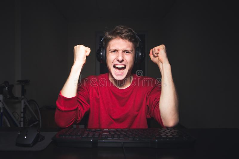 Joyful young man with headphones at home playing a computer game. Gamer happy for the win stock photo