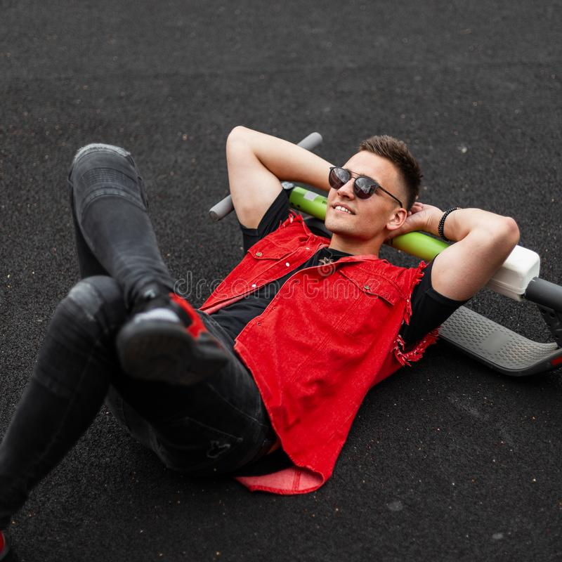 Joyful young man model in a fashionable denim vest in black jeans in sunglasses enjoys a rest lying on the pavement. American guy. Hipster with a  cute smile royalty free stock image
