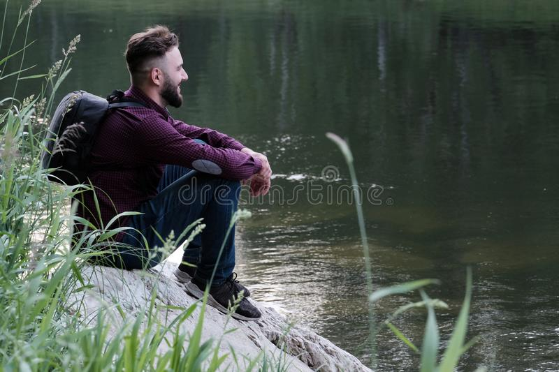 Joyful young man traveler with a backpack in jeans and shirt is sitting on a stone by the river and looking ahead. The stock image