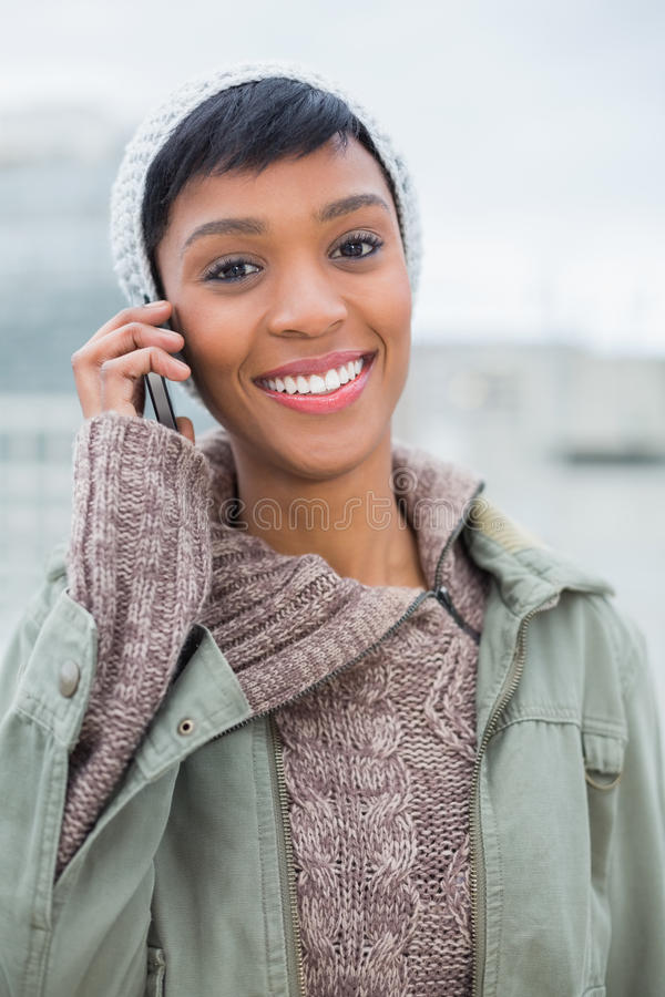 Joyful young model in winter clothes giving a phone call royalty free stock photography