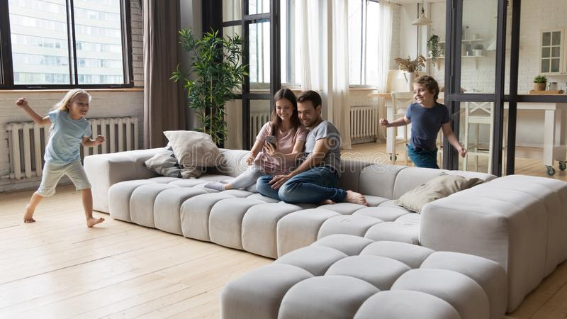 Joyful young parents sitting on sofa while kids running around. stock photo