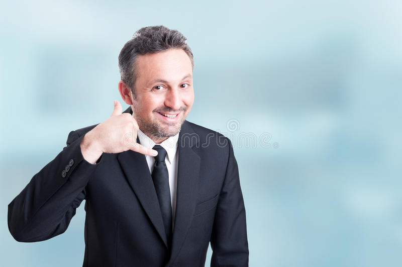Joyful young salesman doing a call me gesture with hand stock photo