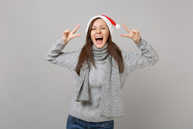 Joyful young Santa girl in gray sweater scarf Christmas hat showing victory sign isolated on grey wall background in stock photography