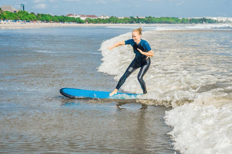 Joyful young woman beginner surfer with blue surf has fun on small sea waves. Active family lifestyle, people outdoor water sport. Lesson and swimming activity stock photo