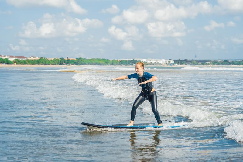 Joyful young woman beginner surfer with blue surf has fun on small sea waves. Active family lifestyle, people outdoor water sport. Lesson and swimming activity stock photography