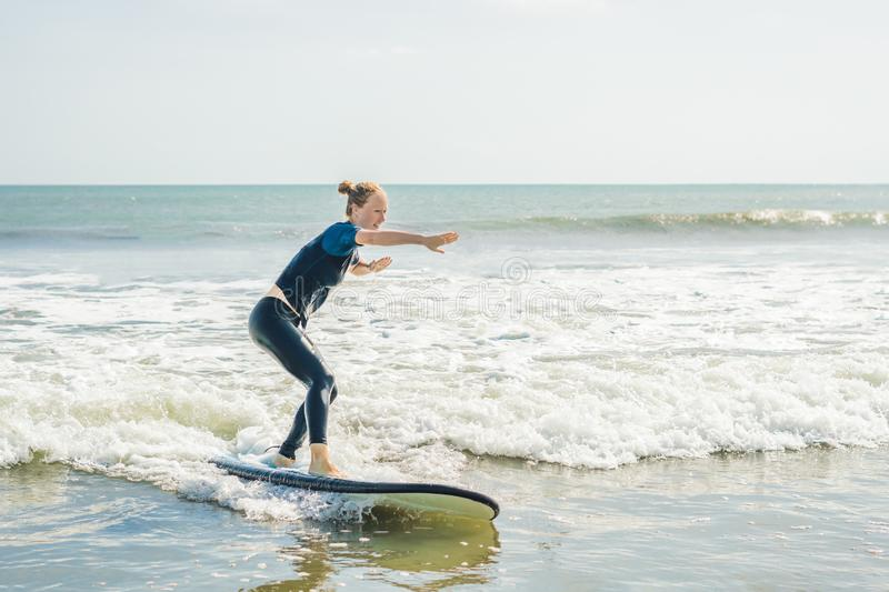 Joyful young woman beginner surfer with blue surf has fun on small sea waves. Active family lifestyle, people outdoor water sport. Lesson and swimming activity royalty free stock image
