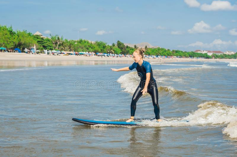 Joyful young woman beginner surfer with blue surf has fun on small sea waves. Active family lifestyle, people outdoor water sport. Lesson and swimming activity royalty free stock photography
