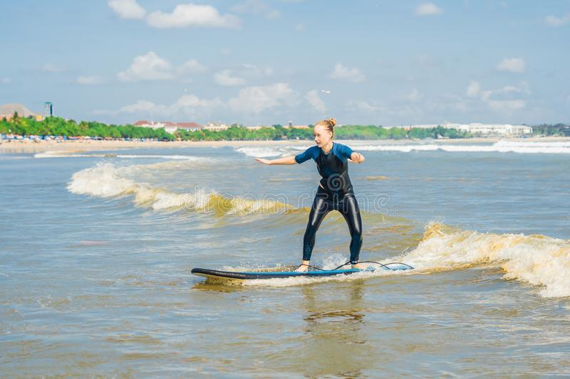 Joyful young woman beginner surfer with blue surf has fun on small sea waves. Active family lifestyle, people outdoor water sport stock photo