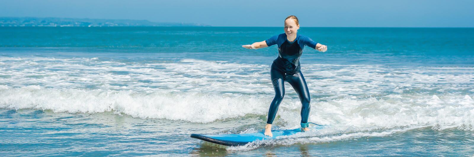 Joyful young woman beginner surfer with blue surf has fun on small sea waves. Active family lifestyle, people outdoor. Water sport lesson and swimming activity royalty free stock photos