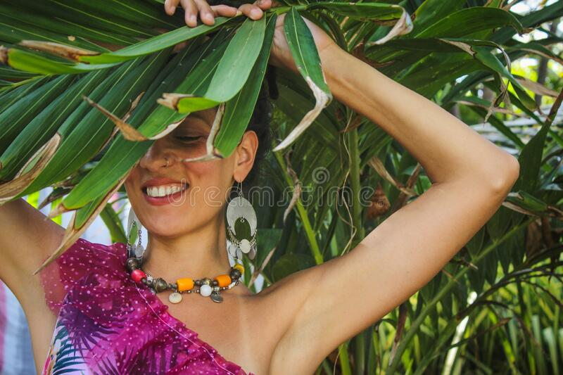 Joyful young woman behind palm leave smiling enjoy in vacation wearing colorful dress necklace and earrings Jamaica stock photos