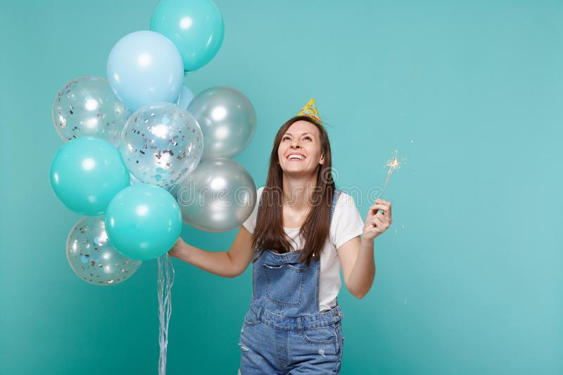 Joyful young woman in birthday hat looking up, holding burning sparkler, celebrating with colorful air balloons isolated. On blue turquoise background. Birthday stock photo