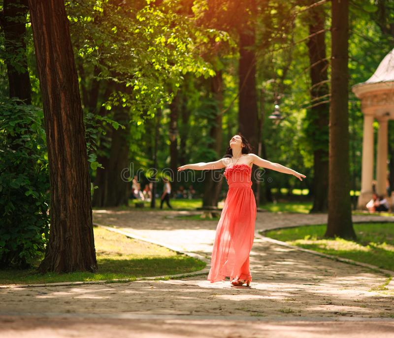 Joyful young woman enjoys dancing in green city park on nature among the trees, concept of freedom and carelessness. Joyful young woman in a green city park on royalty free stock image
