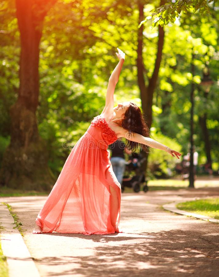 Joyful young woman enjoys dancing in green city park on nature among the trees, concept of freedom and carelessness. Joyful young woman in a green city park on stock photo