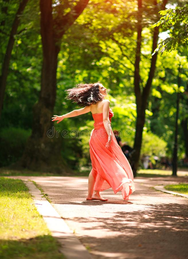 Joyful young woman enjoys dancing in green city park on nature among the trees, concept of freedom and carelessness. Joyful young woman in a green city park on royalty free stock images