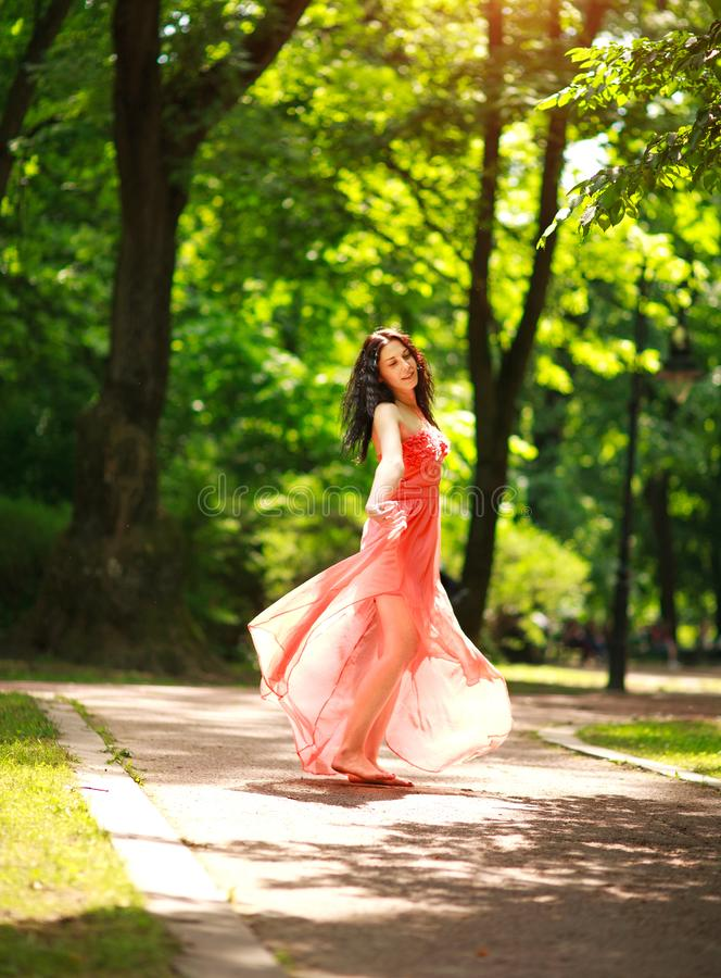 Joyful young woman enjoys dancing in green city park on nature among the trees, concept of freedom and carelessness. Joyful young woman in a green city park on stock photography