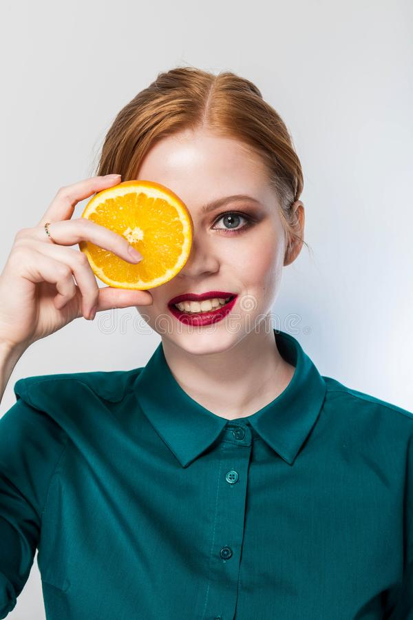 Joyful young woman holding juicy oranges before her eyes. Healthy eating concept. royalty free stock photos