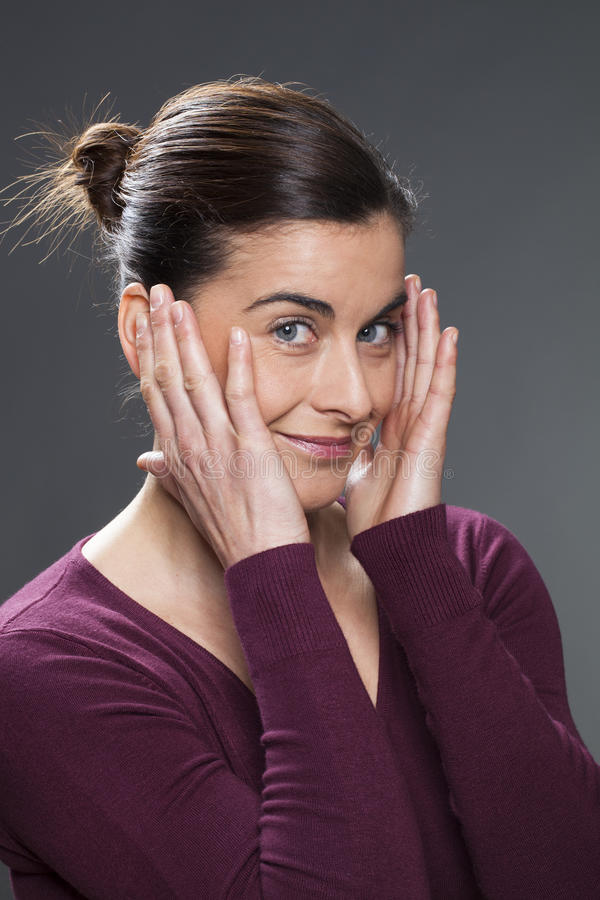 Joyful young woman massaging her temples for skin smoothing stock photos