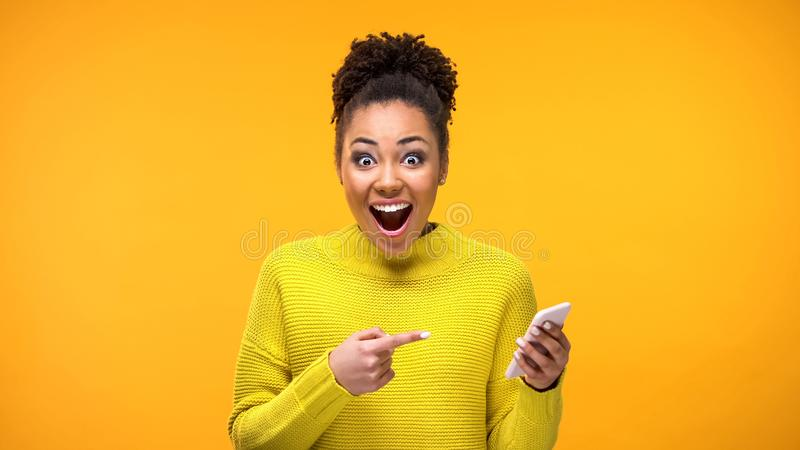 Joyful young woman pointing at smartphone in hand, online shopping application stock photos