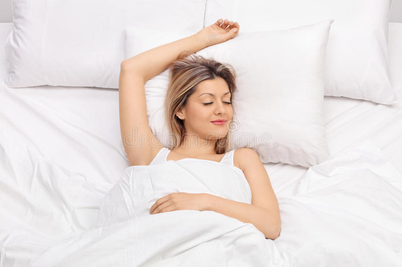 Joyful young woman sleeping on a bed stock image