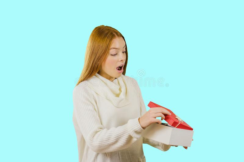 Joyful young woman in white sweater celebrating birthday or Christmas party over isolated background. royalty free stock image