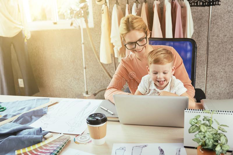 Mother and son in craft room. Joyful young women and her son working on laptop at table in craft room royalty free stock photo