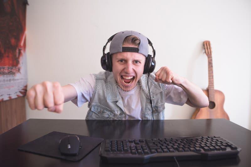 Joyfulmgamer, das zu Hause Videospiele auf einem Computer spielt Gamer in den Kopfhörern und in der Kappe ist glücklich stockfotografie