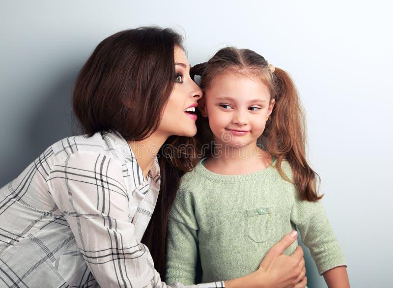 Joying年轻母亲耳语秘密对她滑稽做鬼脸 免版税库存照片