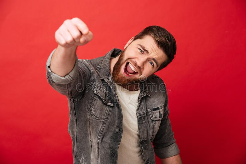 Joyous cheerful man 30s in jeans jacket smiling and pointing ind. Ex finger on camera over red background royalty free stock photo