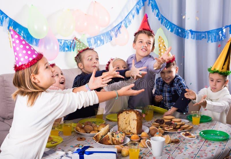 Joyous jongens en meisjes gelukkig om friend's verjaardag te vieren royalty-vrije stock foto's