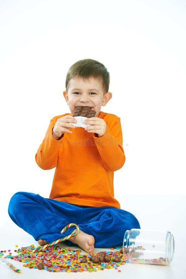 Joyous kid eating chocolate sitting cross-legged stock images