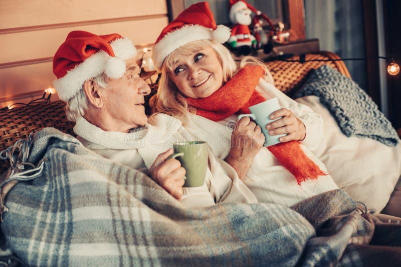 Joyous oud paar op bank tijdens vakantietijd royalty-vrije stock foto's