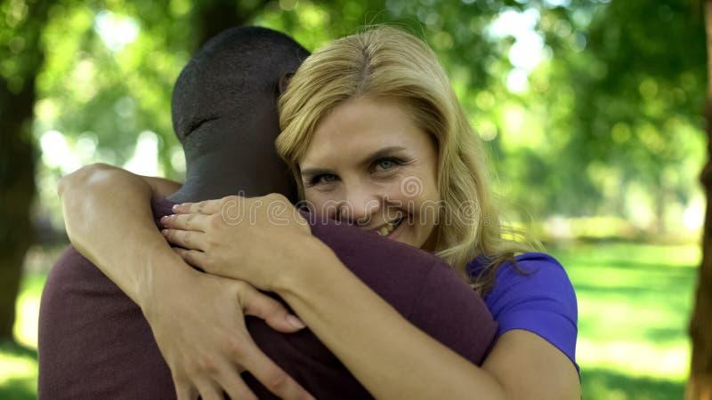 Joyous vrouw die passionately Afro-Amerikaanse vriend, gelukkig paar omhelzen stock afbeeldingen
