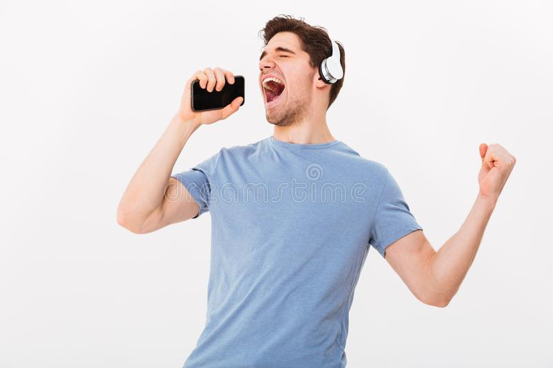 Joyous young man 30s in casual t-shirt listening to music via wi royalty free stock images