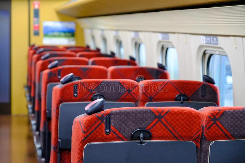 JR red seat on Japanese train JR shinkungzen colorful aisle seat E, JR train park on the track arrange to next station,seats are e. Mpty have no passengers and stock photography