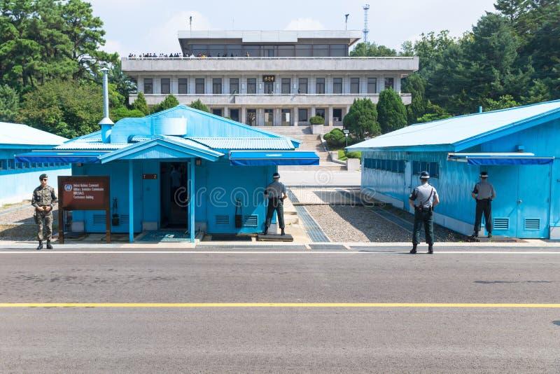 JSA в пределах DMZ, Кореи - 8-ое сентября 2017: Солдаты ООН и солдаты на солнечный день перед голубыми зданиями на северном жител стоковые изображения rf