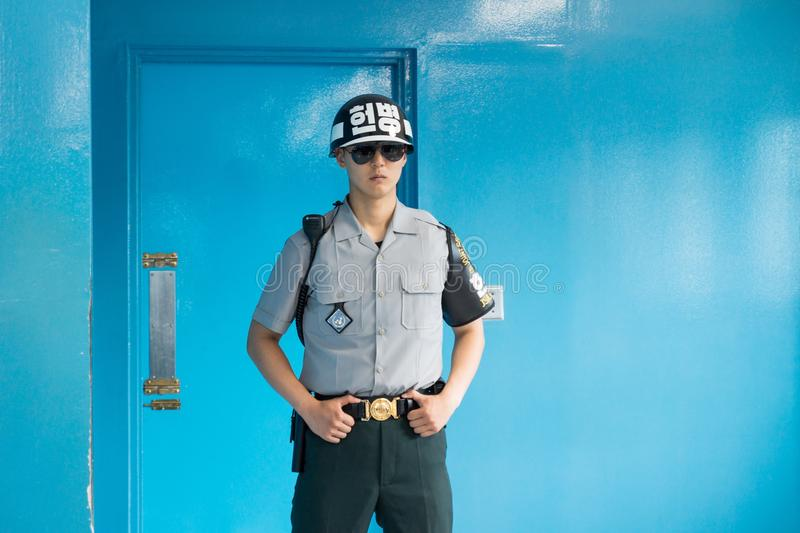 JSA within DMZ, Korea - September 8 2017: UN soldier in blue building at North South Korean border guarding the door to North Kore royalty free stock images
