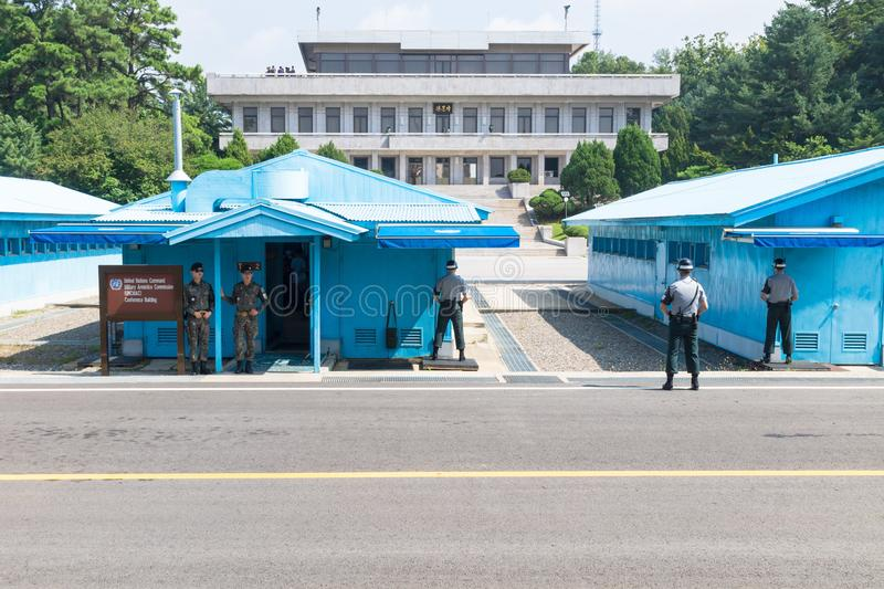 JSA within DMZ, Korea - September 8 2017: UN soldiers and 2 soldiers with camouflage clothes in front of blue buildings at North S stock image