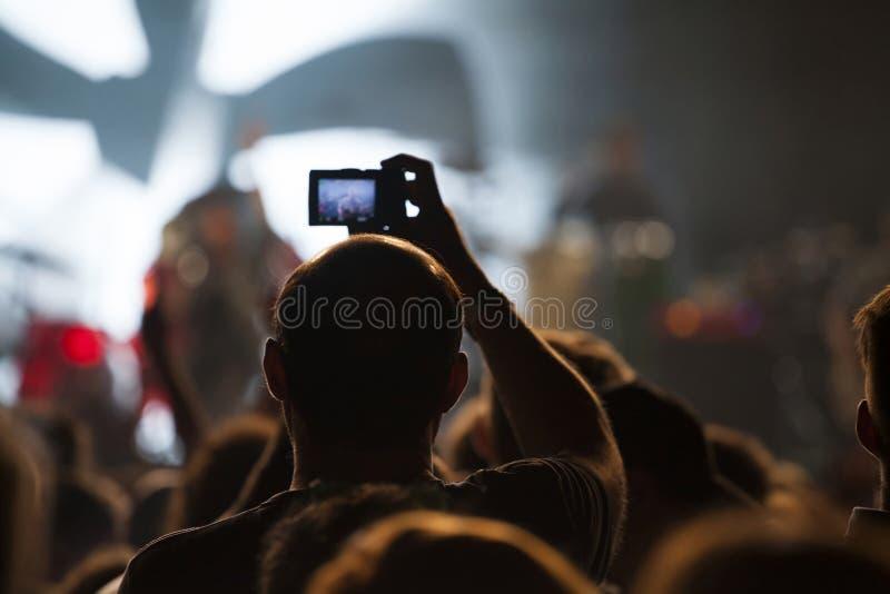 Jubelnde Menge an einem Konzert gefilmt auf Kamera stockfotografie