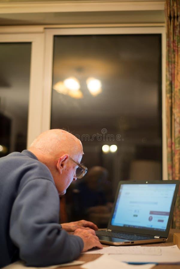 Jubilado usando un ordenador port?til para comprobar sus carteras de participaciones, Hampshire, Inglaterra, U K imágenes de archivo libres de regalías