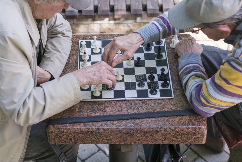 Jubilados activos, viejos amigos y tiempo libre, dos mayores que se divierten y que juegan al juego de ajedrez en el parque Los v foto de archivo