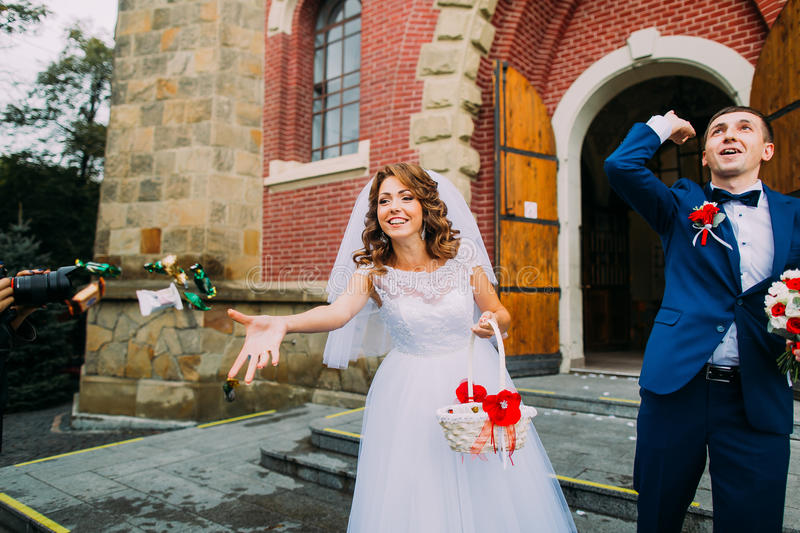 Jubilant bride and groom leaving the church after a wedding ceremony royalty free stock photo