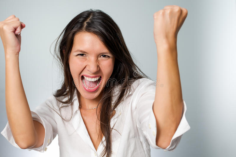 Jubilant young woman cheering her success raising. Her fists in the air in excitement and elation at her achievement or victory stock photos